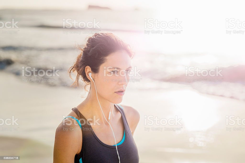 Sporty young woman looking away at beach stock photo