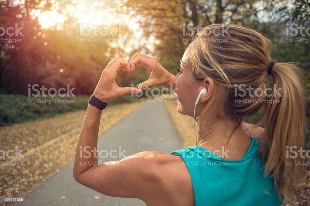 Sporty young woman makes heart shape finger frame at sunset stock photo