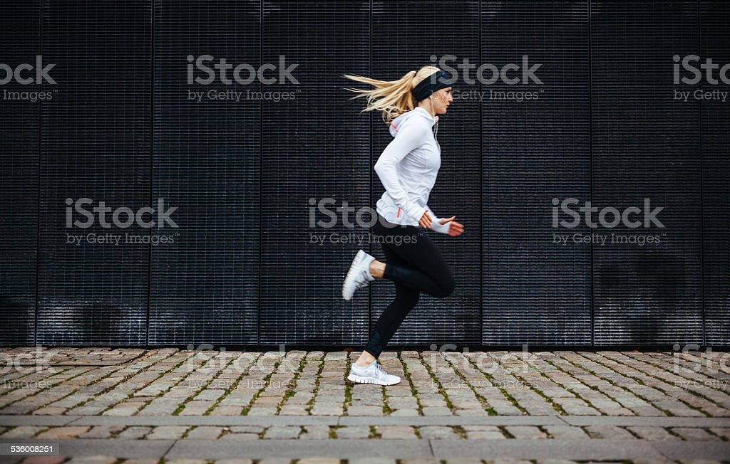 Sporty young woman running on sidewalk in morning stock photo