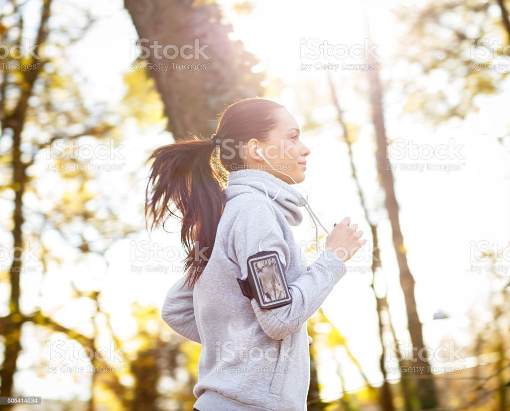 Sporty young woman running outside. stock photo