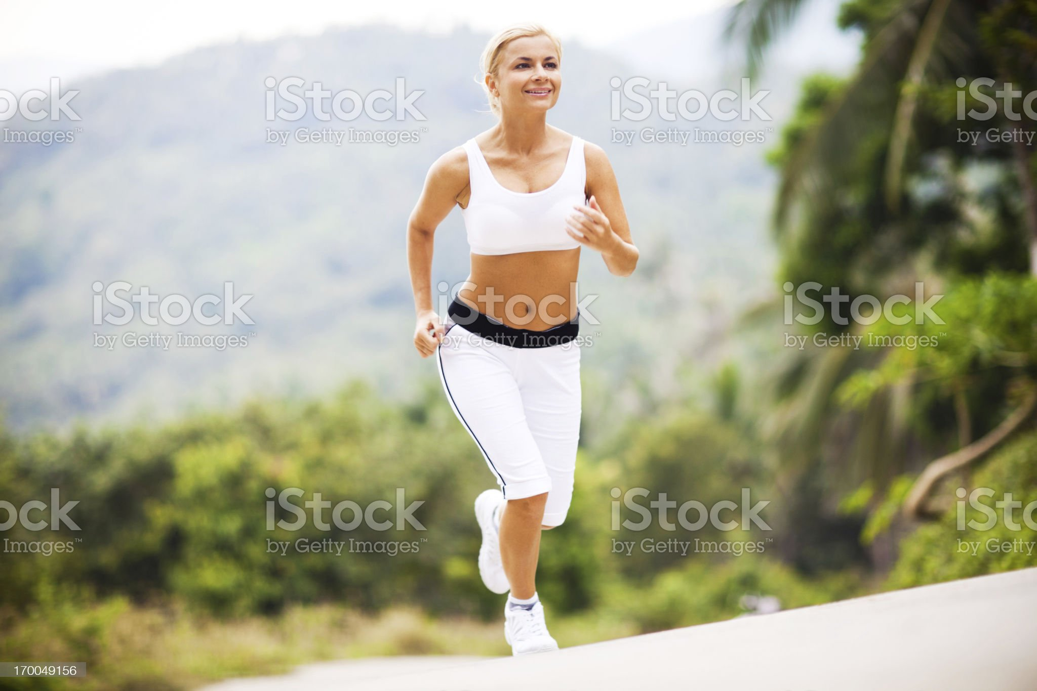 Sporty young woman running up the hill. royalty-free stock photo