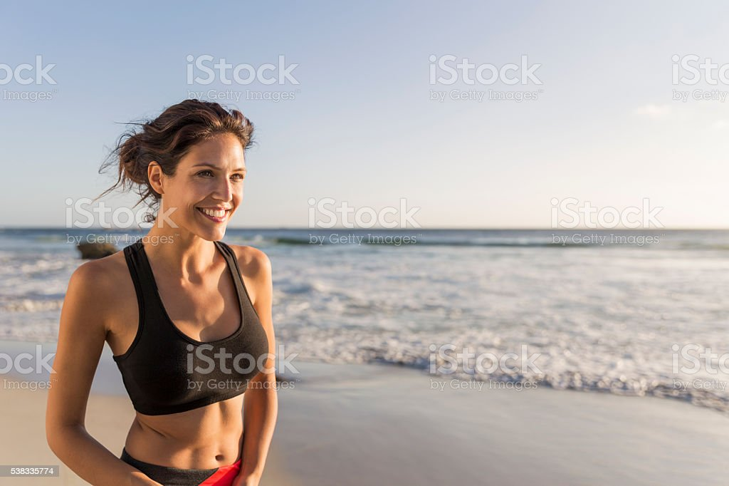 Sporty young woman smiling at beach stock photo