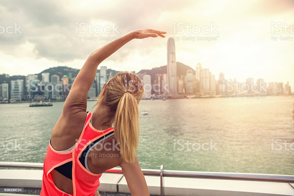 Sporty young woman stretching after jogging in Hon Kong stock photo