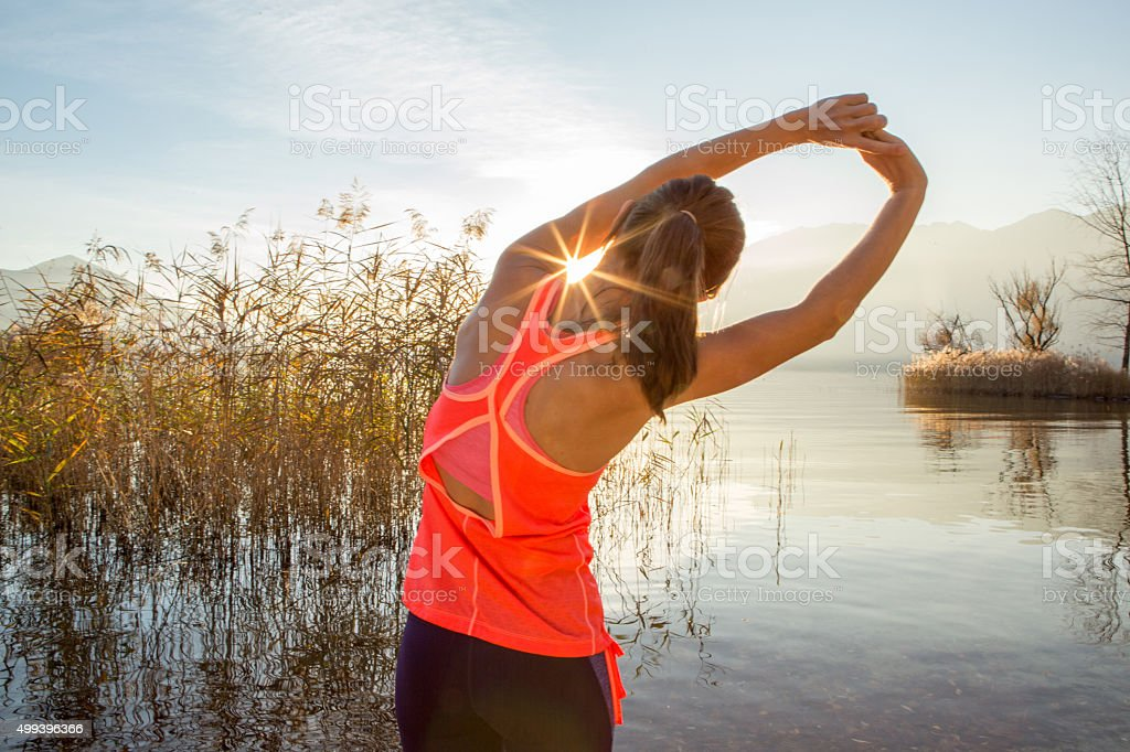 Sporty young woman stretching after jogging outdoors stock photo