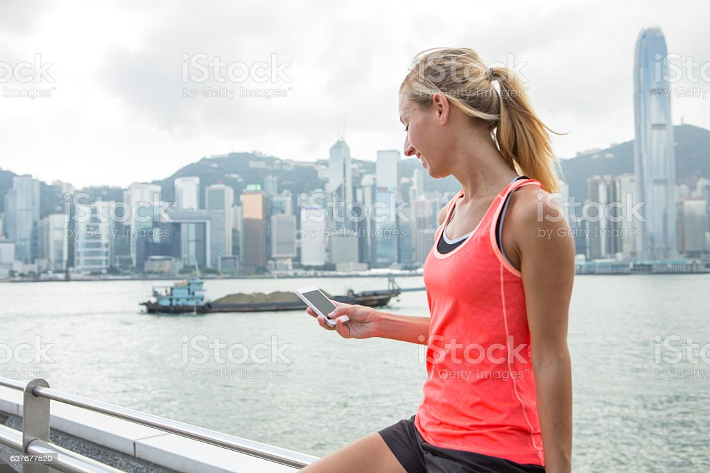 Sporty young woman text messaging on smart phone, Hong Kong stock photo