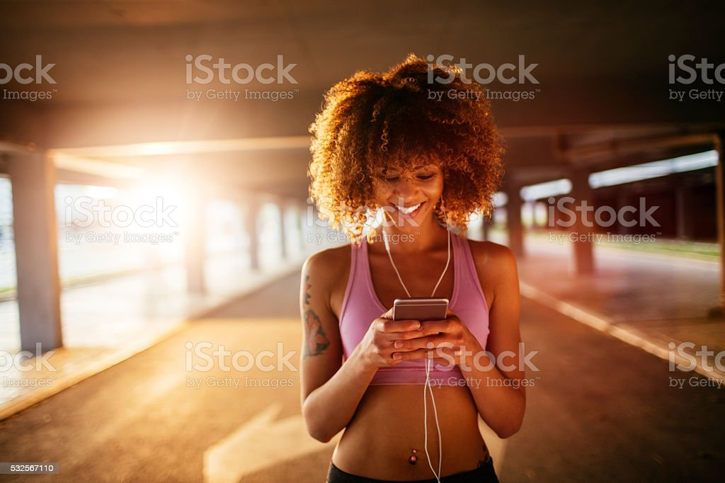 Sporty young woman using a phone stock photo