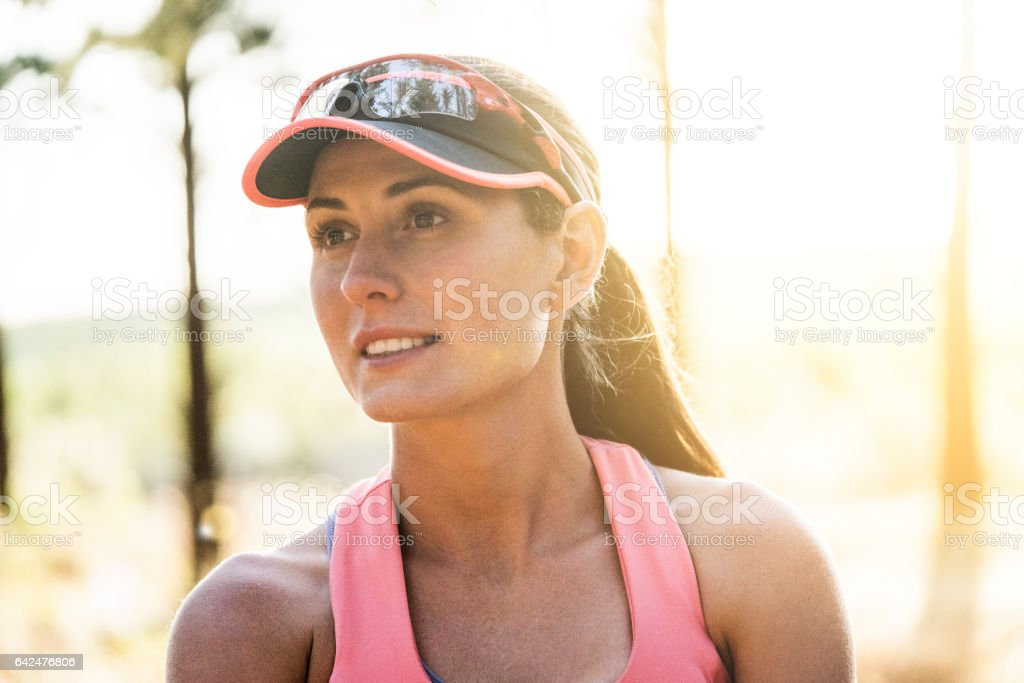 Sporty young woman wearing sun visor hat outdoors stock photo
