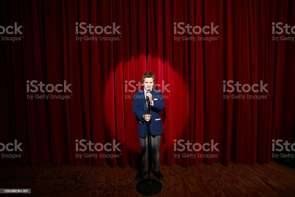 Spotlight on on boy (11-13) holding microphone on stage, portrait stock photo