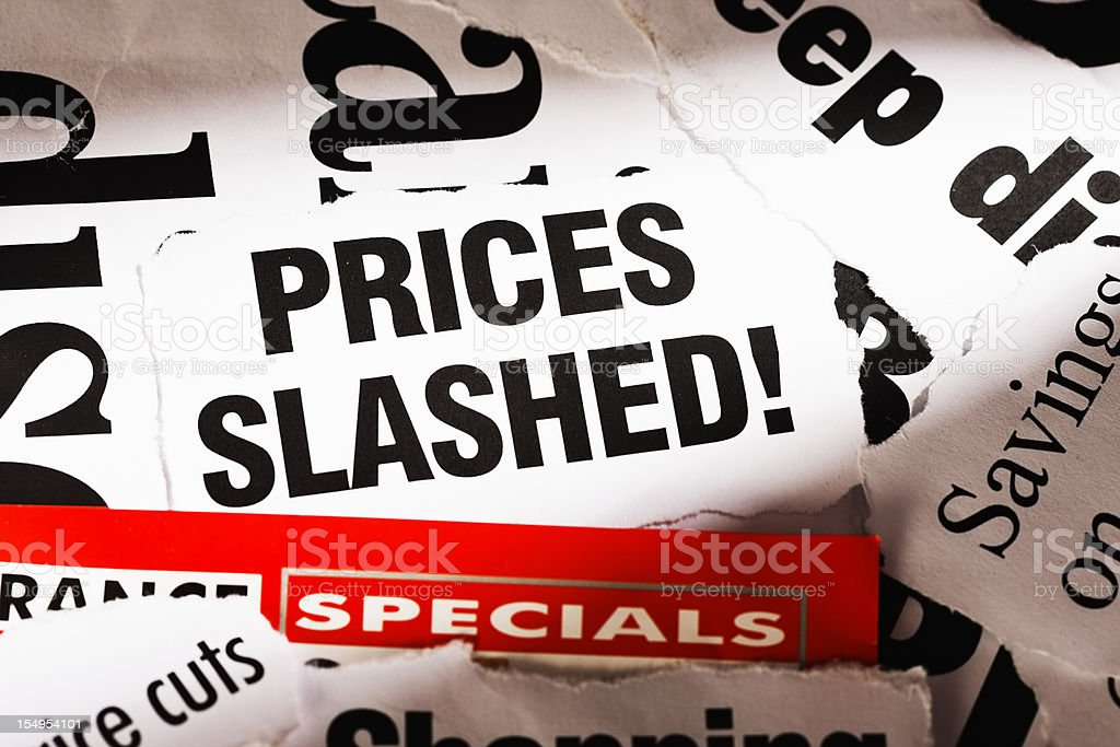 Spotlight on slashed prices in pile of press cuttings stock photo