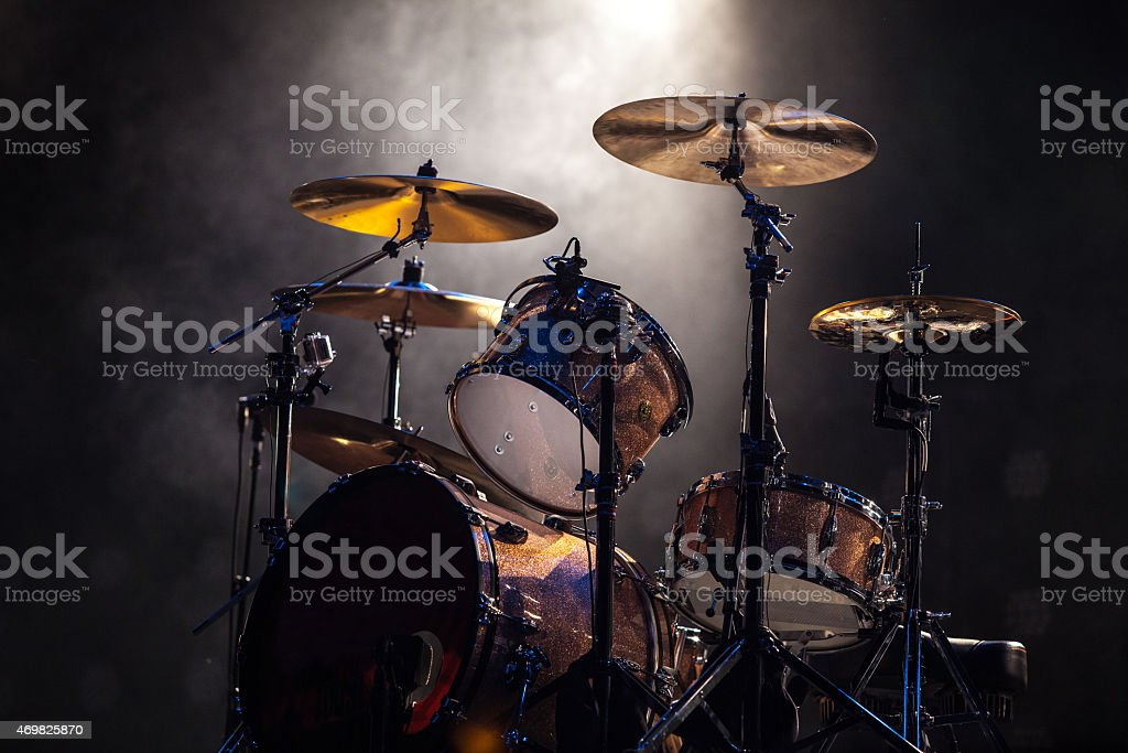 Spotlighted rock and roll drum set on gray background stock photo