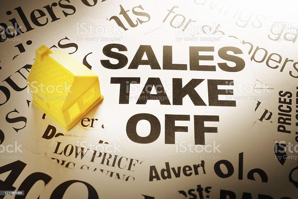 Spotlit yellow house on optimistic sales headlines royalty-free stock photo