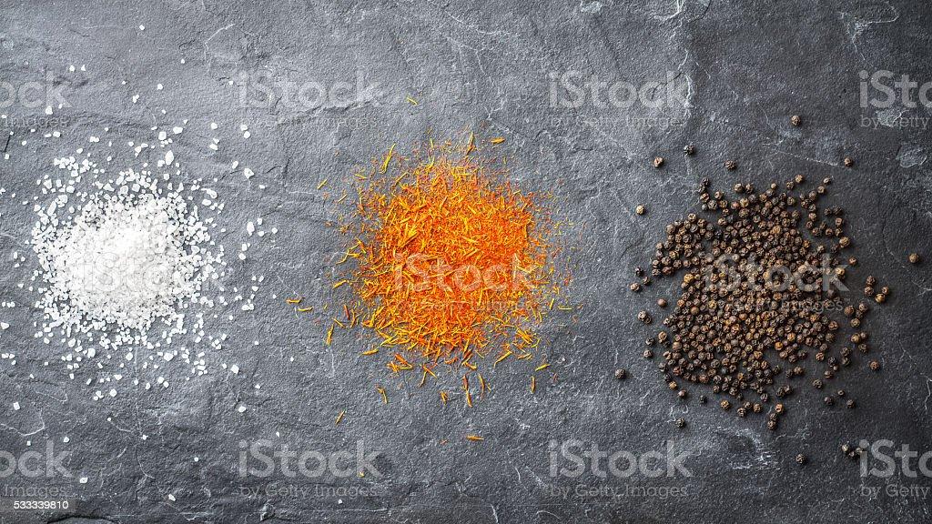 Spots salt, saffron, pepper on a gray stone stock photo