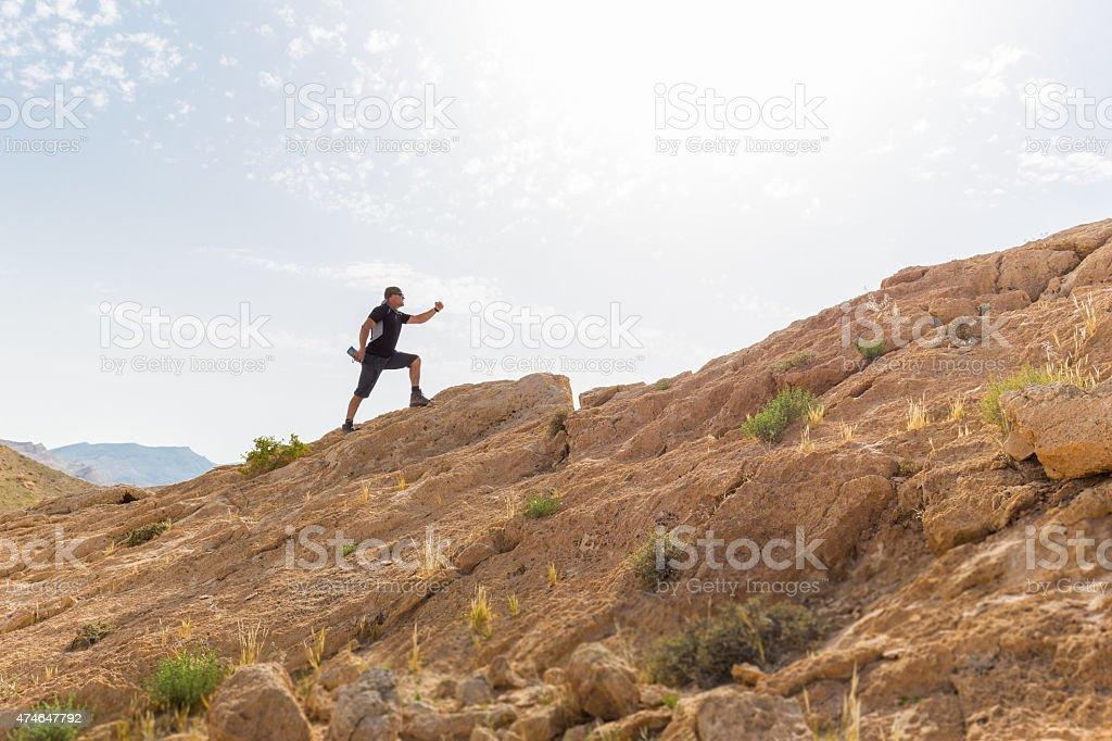 Spotsman running up stone desert hill. stock photo