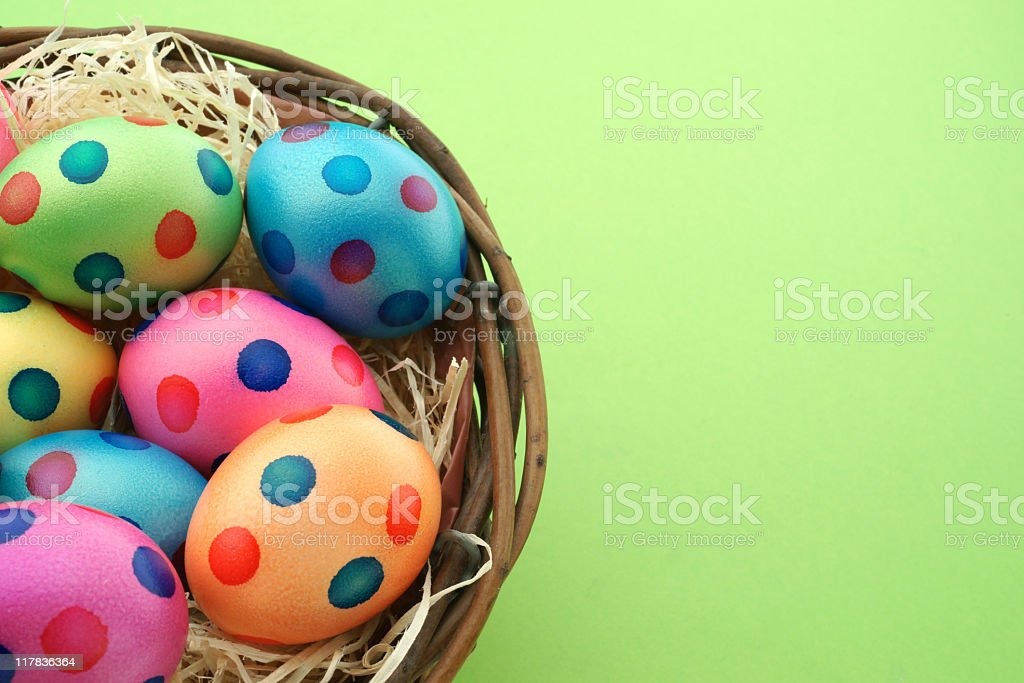Spotted Easter eggs in a basket on a green backdrop royalty-free stock photo