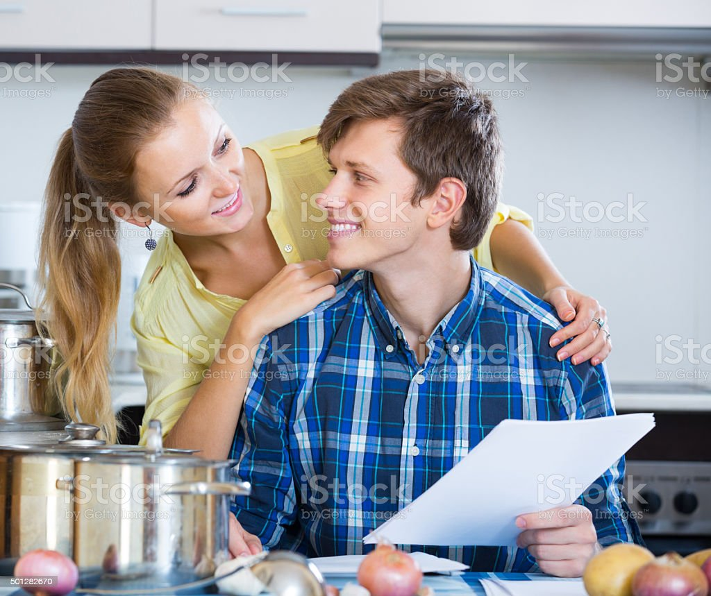 spouses signing documents and smiling at kitchen stock photo