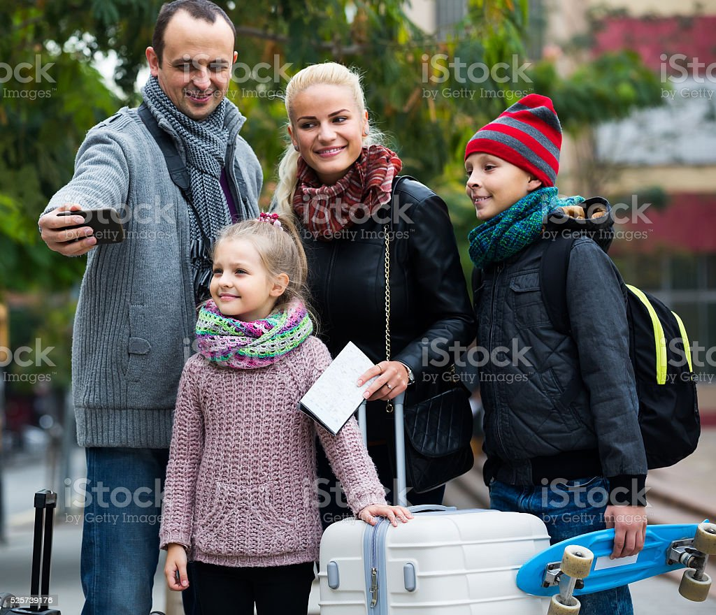 spouses with children shooting mutual portrait on cell phone stock photo
