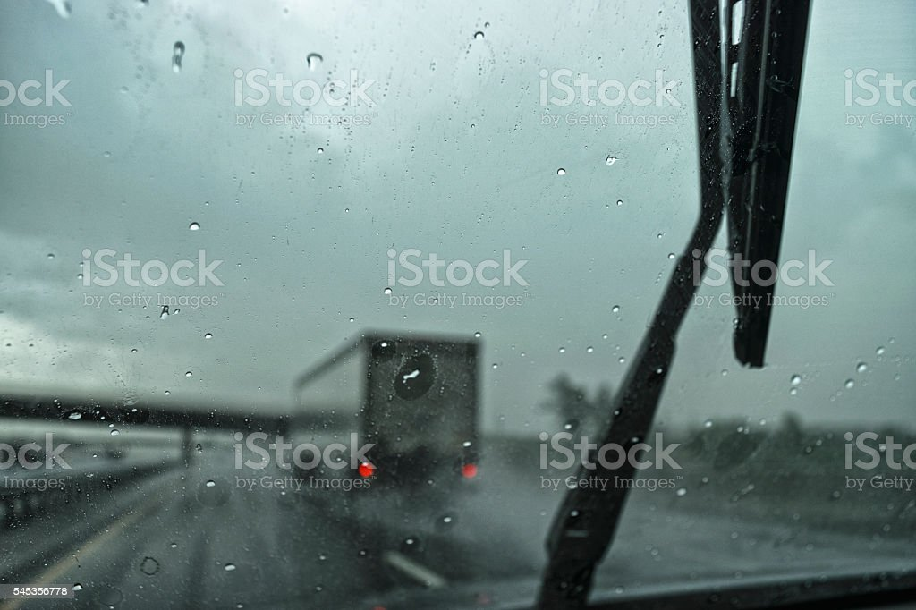 Spray from tractor trailer in a heavy rain on highway stock photo