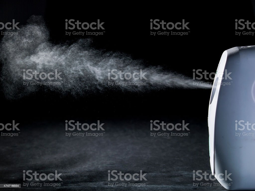 spray in front of black background stock photo