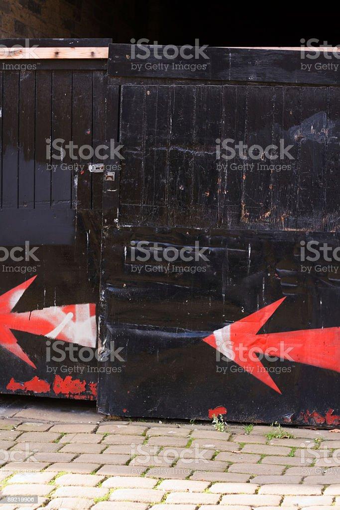 Spray Painted Arrow on Black Gate stock photo