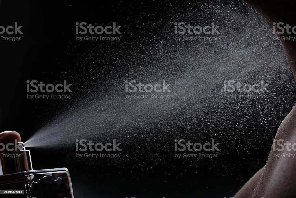 spray perfume on body stock photo