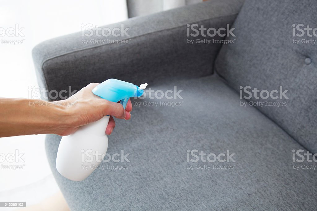 Sprayed air freshener in hand on home interior background stock photo