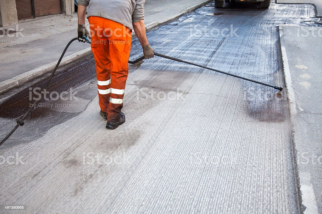 Spraying asphalt on the unpaved surface stock photo