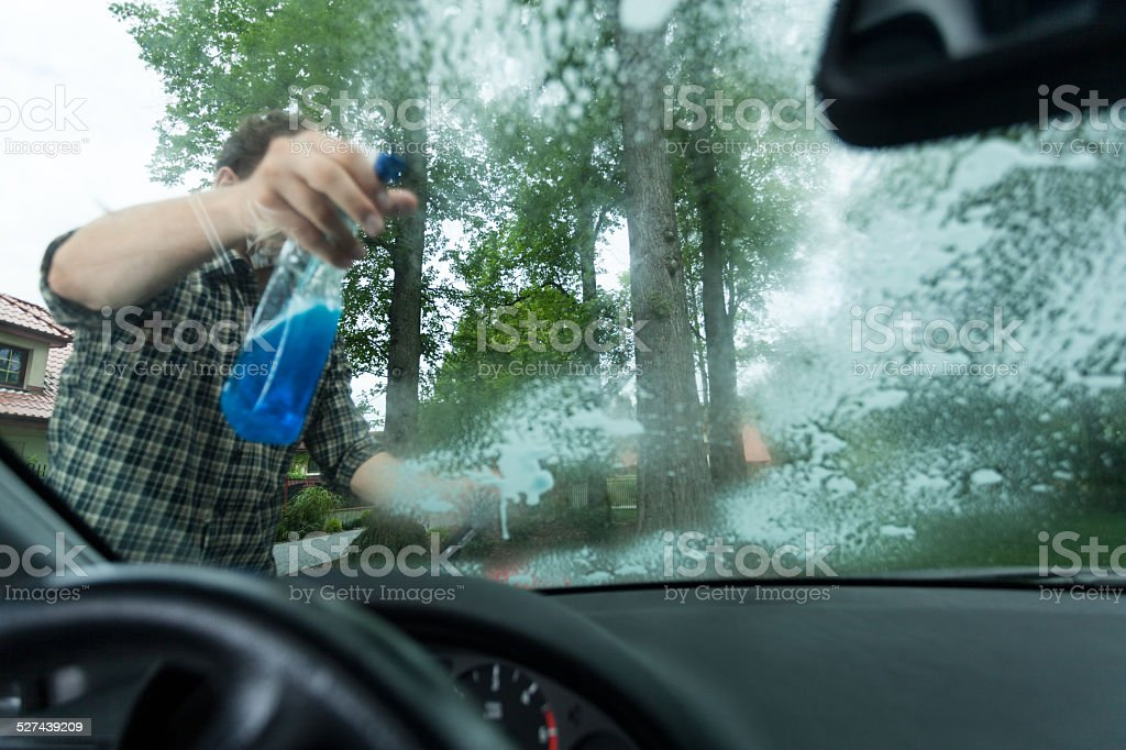 Spraying detergent on a window stock photo