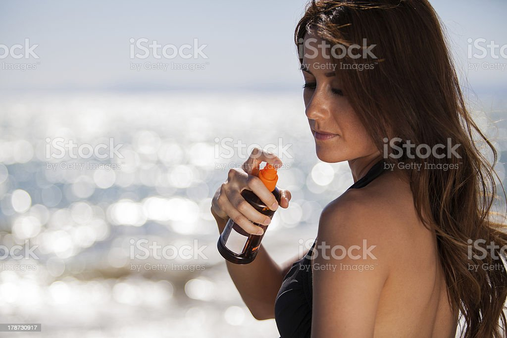 Spraying some tanning lotion royalty-free stock photo