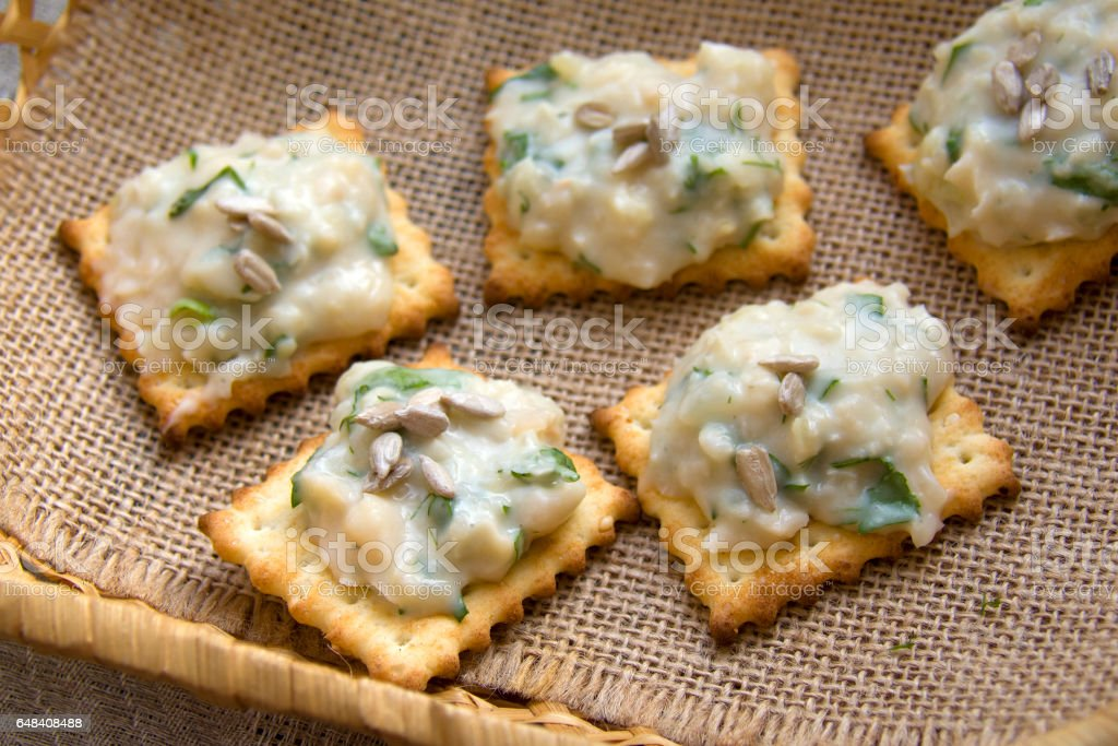 spread with french beans and parsley, on crackers stock photo