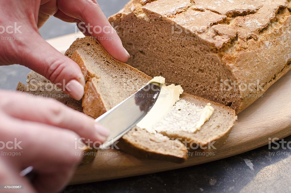 Spreading butter on freshly baked rye bread stock photo