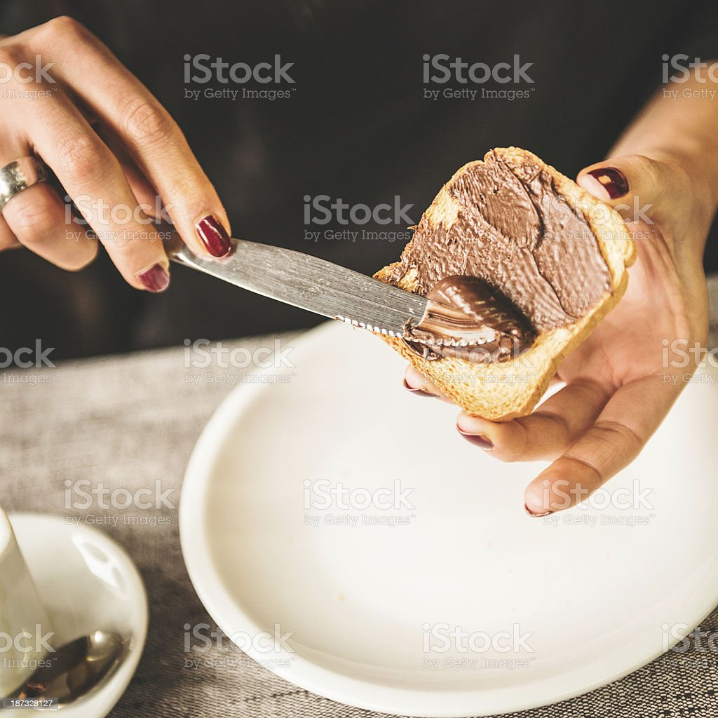spreading jam on the baked bread stock photo