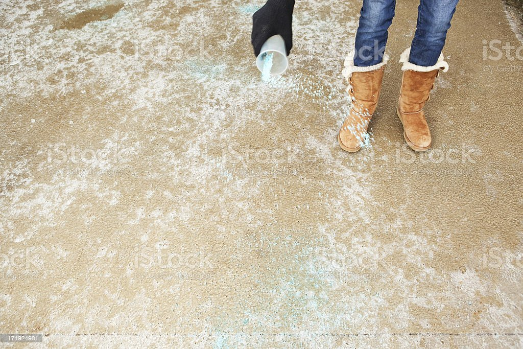 Spreading Salt on a Icy Winter Driveway stock photo