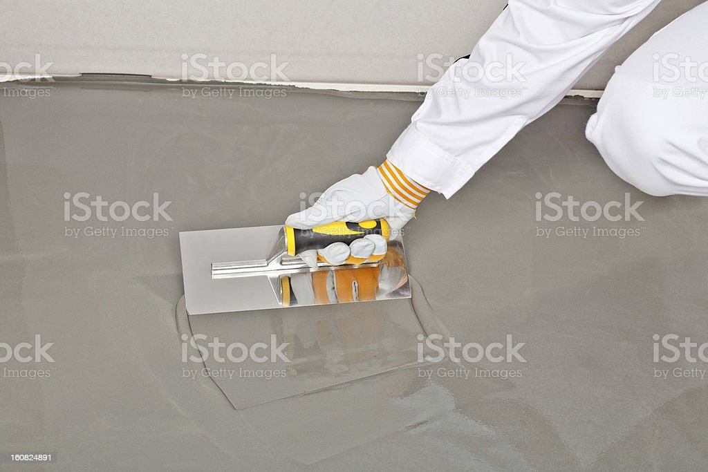spreading self leveling compound with trowel royalty-free stock photo
