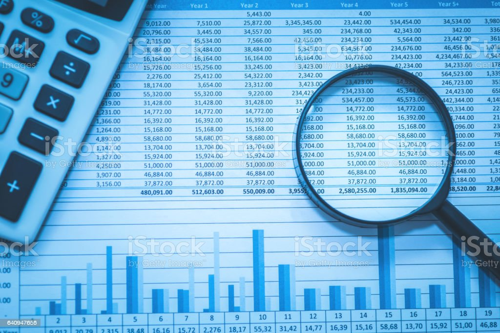 Spreadsheet bank accounts accounting with calculator and magnifying glass. stock photo