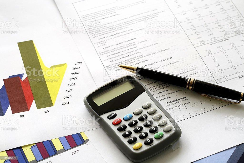 A spreadsheet, graphs, pen and calculator stock photo