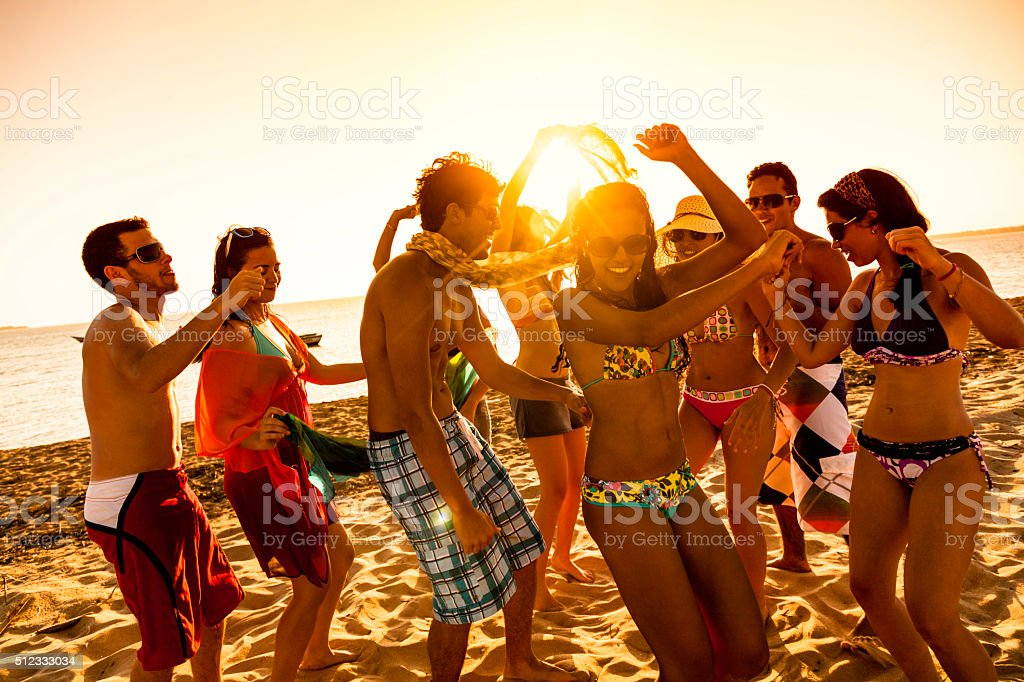 Spring break backlit group of young people dancing on beach stock photo