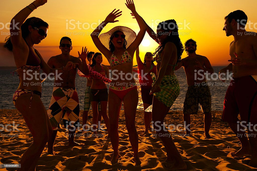Spring break group of young people dancing on a beach royalty-free stock photo