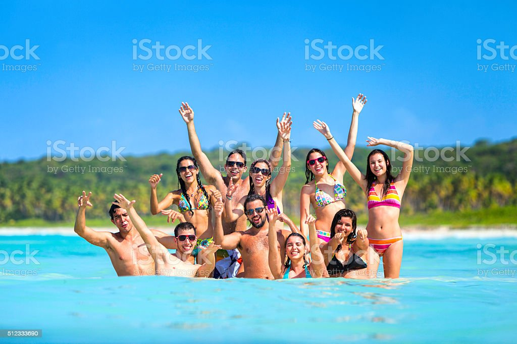 Spring break group of young people having fun tropical beach stock photo