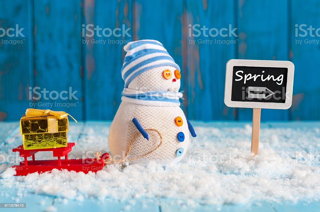 Spring change winter background. Snowman with gift and red sled stock photo