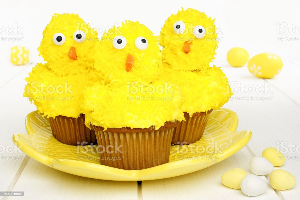Spring chick cupcakes on yellow plate with Easter eggs stock photo