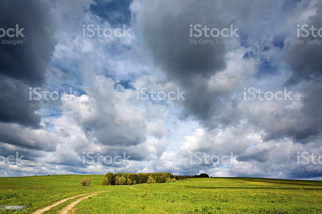 Spring clouds over rural meadow royalty-free stock photo