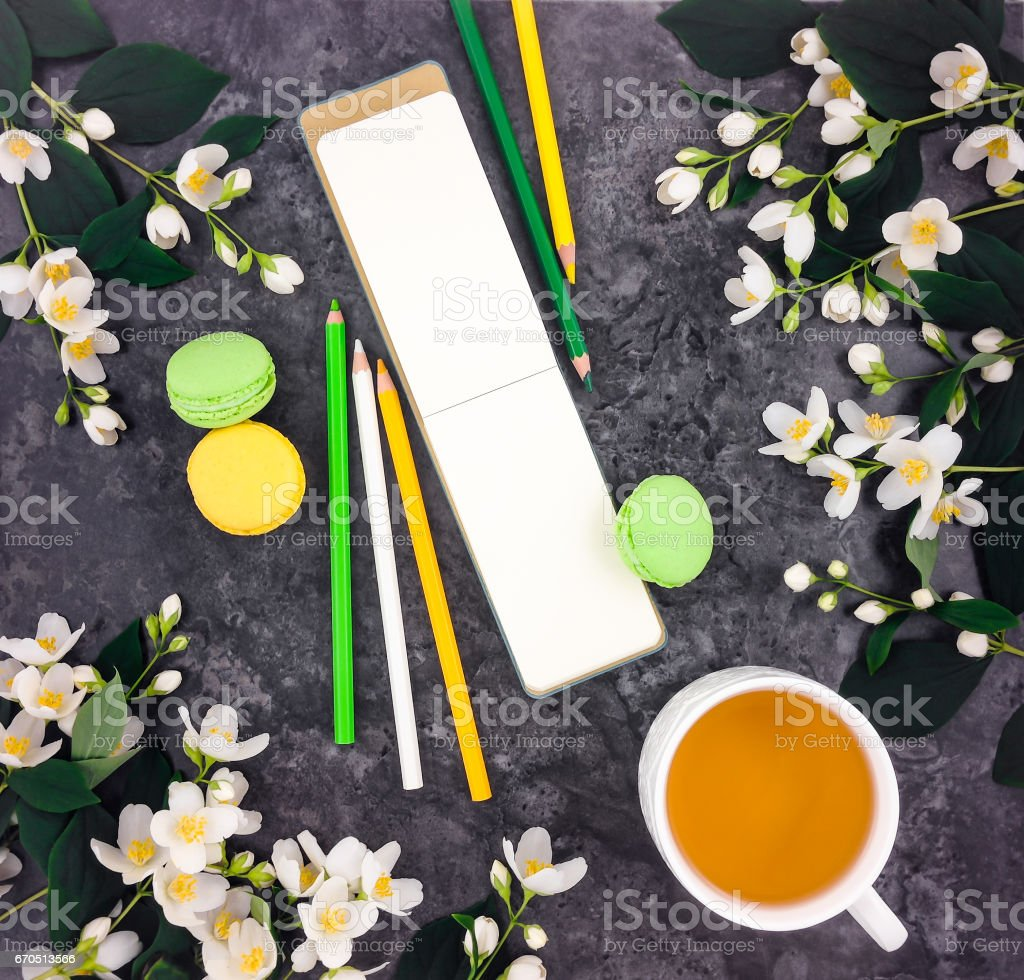 Spring composition of cup of tea, sketchbook and flowers on stone marble table, flat lay stock photo