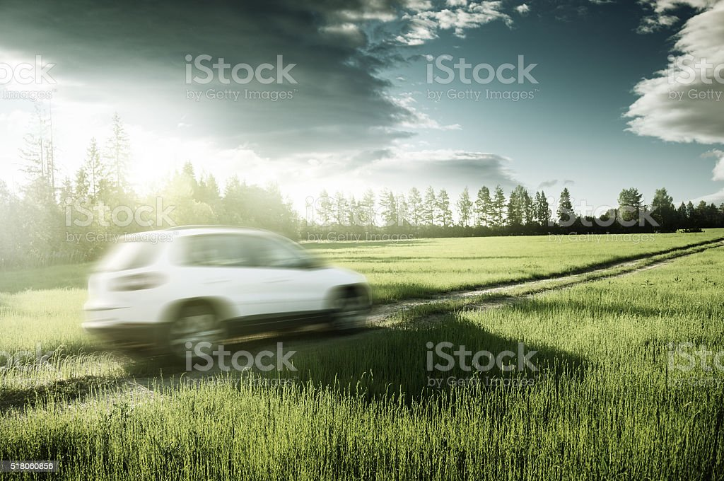 spring field and blured car on ground road stock photo