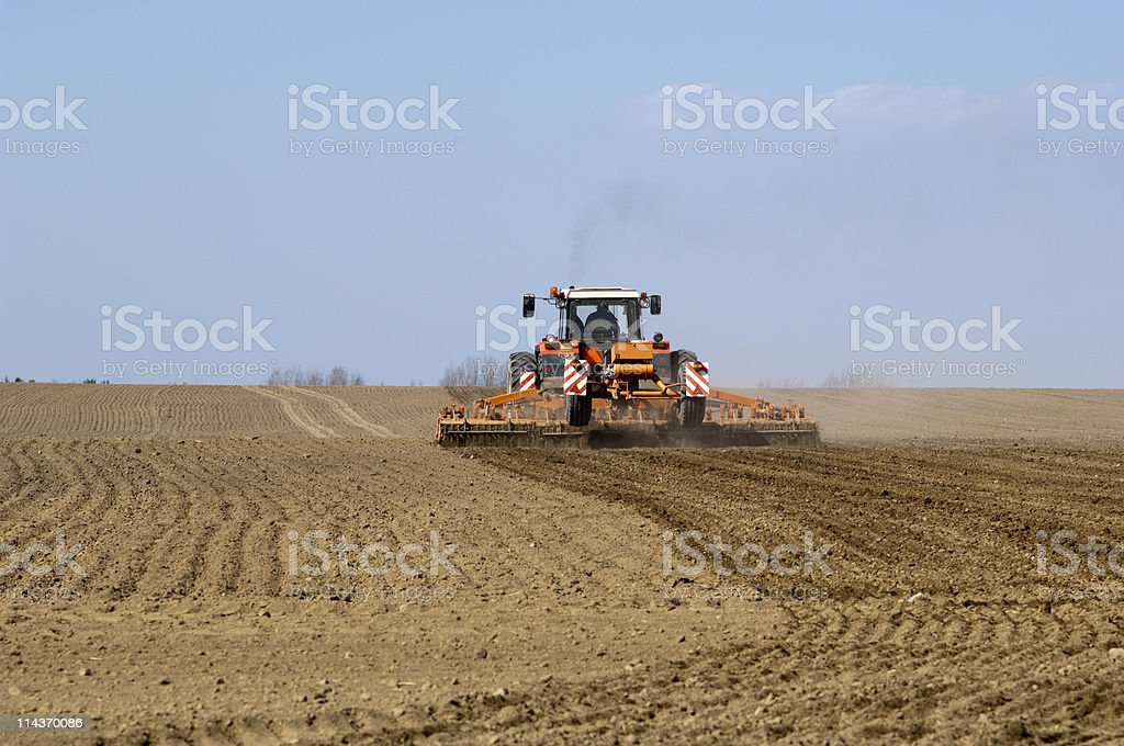 Spring field with tractor and cultivator royalty-free stock photo