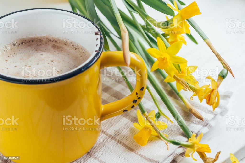 Spring flowers daffodils with a cup of coffee, cappuccino, close-up stock photo