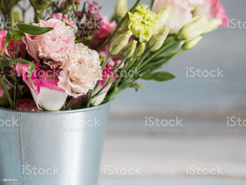 Spring flowers in small tin bucket. Bunch of different spring flowers in small tin bucket. Rustic wooden background stock photo