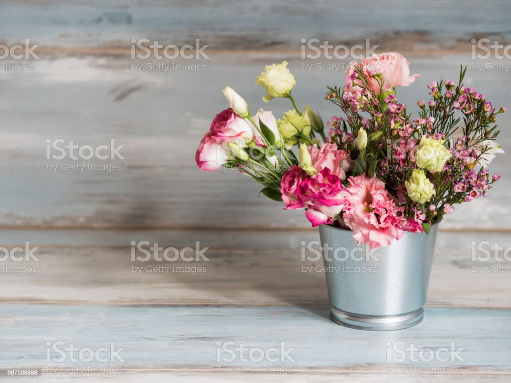 Spring flowers in small tin bucket. Bunch of different spring flowers in small tin bucket. Rustic wooden background. Free space left stock photo