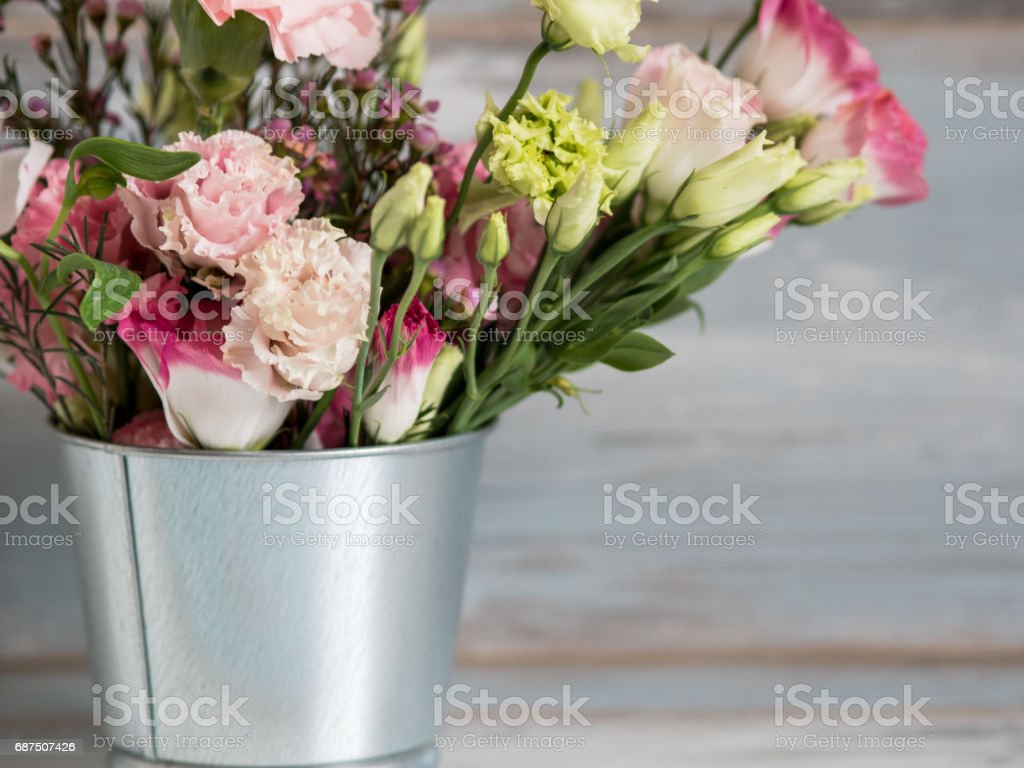 Spring flowers in small tin bucket stock photo