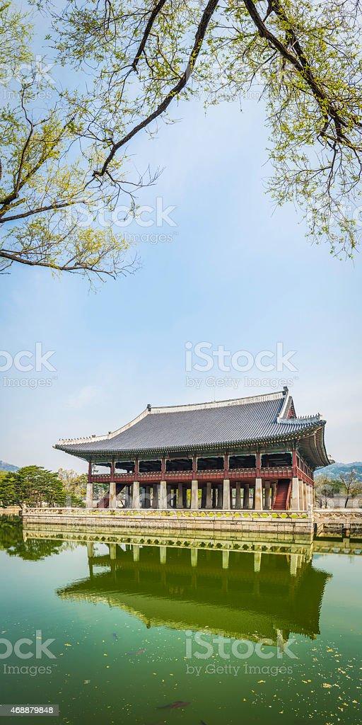 Spring foliage framing temple reflecting in tranquil lake Seoul Korea stock photo