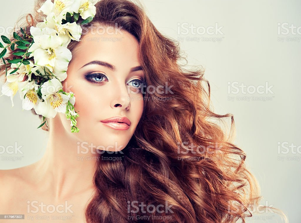 Spring freshness. Girl with delicate pastel flowers in hair stock photo